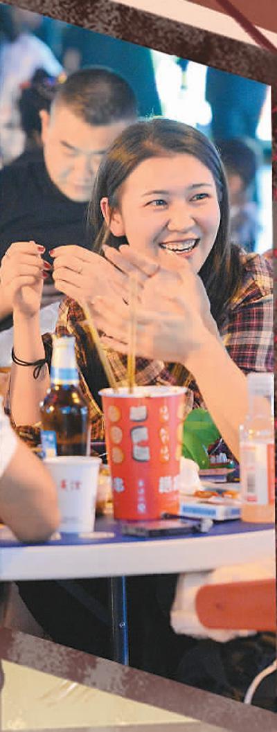 人们在新疆乌鲁木齐市五一星光夜市上品尝美食。   新华社记者 丁 磊摄