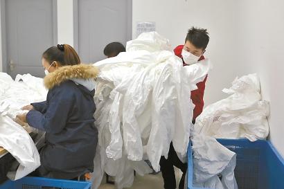 昨天,上海诚格安全防护用品有限公司生产车间,工人们正加班加点赶制防护服。目前,诚格每天产能在1600件左右,公司将边生产边调整,力争短期内能每天生产9000件。本报记者 赖鑫琳 摄