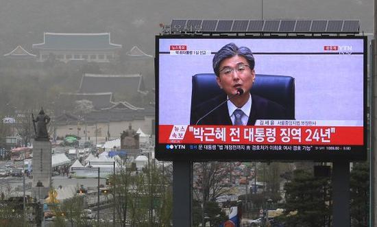 青瓦台附近的屏幕,直播朴槿惠一审宣判的画面