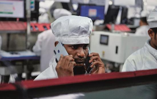 在印度诺伊达的一家手机工厂里,工人正在检测手机。图/法新