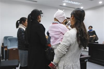 昨日,一名当事女员工抱着孩子在法庭上接受记者采访。新京报记者 王贵彬 摄