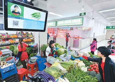2017年11月29日,在安徽合肥瑶海区胜利智能农贸市场,市民在扫码支付。张大岗摄(新华社发)