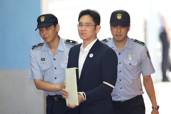 2017年8月25日星期五,韓國三星電子副會長李在鎔(中)由監獄看守押送到首爾中央地方法院。Chung Sung-Jun/Pool via Bloomberg