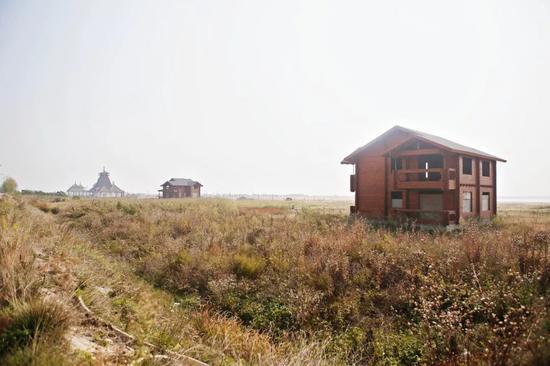 """一片曾经喧闹的海边沙滩游乐场正在被野草""""吞噬""""。"""