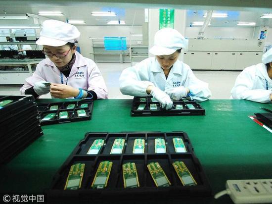 本文头图:2010年11月10日,江西省九江市共青城工业园区,赛龙通信公司的工作人员在进行手机芯片生产作业。(视觉中国授权)
