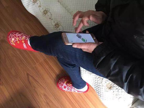 """母亲在用手机玩""""跳一跳""""小游戏。"""