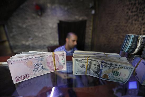 叙利亚壹处钱币兑换点柜台上摆放的里弹奏和美元。视觉中国 图