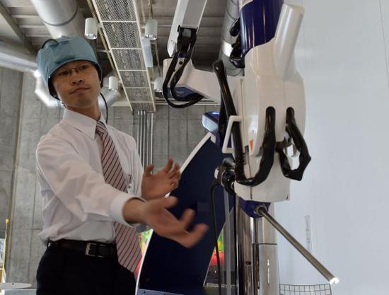 在日本东京,日本一家医疗器械公司的工程师示范操作世界第一台内窥镜机器人。新华社/法新