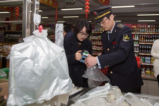 """3月17日,上海株洲路联华超市,质监执法人员用测厚仪对""""三无""""塑料袋进行测量。 澎湃新闻记者 朱伟辉 图"""