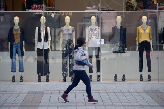消费在中国GDP中的份额开始上升。图为北京街头一名行人从商场橱窗前走过。(法新社)