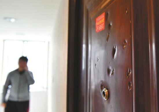 小杨住处的防盗门上有10多个小坑,疑似被利器砸过,门锁也被撬变形。 来源:华西都市报