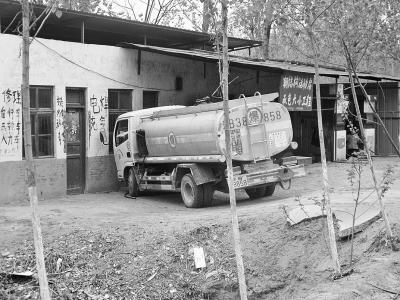 一辆油罐车正在给一处非法加油点送油