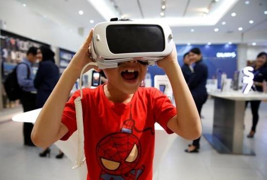 图为一位少年在三星展厅振奋地试用虚构理想设施三星Gear VR。来历:路透