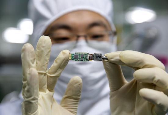 """材料图像:2015年11月7日,一位研讨人员在位于西安的试验室外向记者展现光子集成芯片。光子集成芯片是经过我国自立研制的光电子集成范畴技能制作的芯片,可完成对传统集成电路的""""弯道超车"""",推进我国在光电子集成电路范畴从""""跟跑者""""向""""领跑者""""变化。新华社记者 金立旺 摄"""