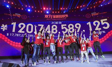 """11月12日,阿里巴巴集团实况显示""""双11""""促销活动网购交易额的屏幕前,相关人士欢呼庆祝。摄于中国广东省深圳市。(共同社)"""