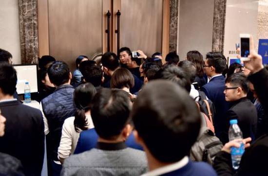 贾跃亭闭门演讲时,门外挤满了人,不时有人咚咚砸门,要求进场。摄影|史小兵