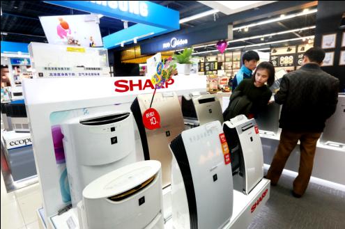 2015年12月5日,北京苏宁云商联想桥店,雾霾再度来袭,顾客在选购夏普空气净化器,减少室内PV2.5等污染,洁净空气。资料图