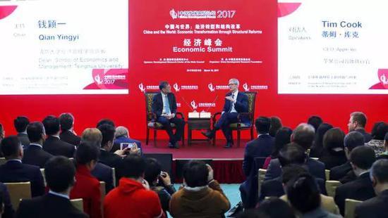"""3月18日,清华大学经济管理学院院长钱颖一(台上左)与苹果公司首席执行官蒂姆·库克(台上右)在峰会的""""全球化新环境下的创新与创业""""分会场展开对话。新华社记者 才扬 摄"""
