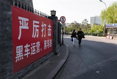 """""""五一""""假期首日。北京德胜门公交车站,""""严厉打击黑车运营、黑导游""""的宣传牌。 新京报记者 李强 摄"""