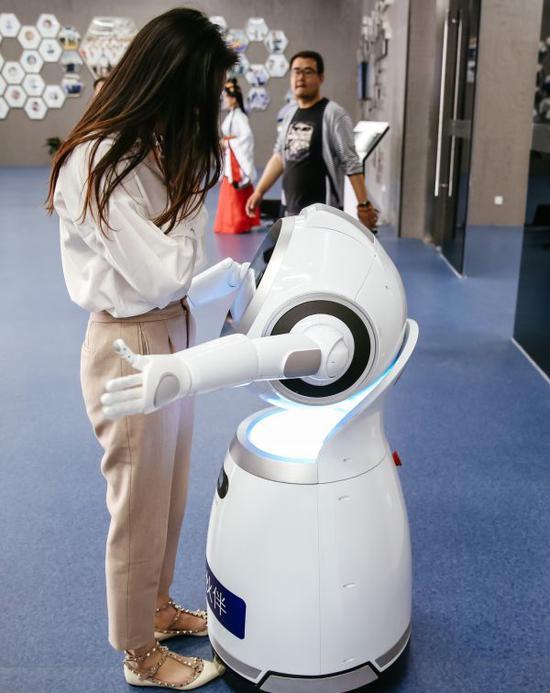 """资料图片:""""云朵""""智能互动机器人在拥抱一位观众。它能与人对话交流,还能表演唱歌跳舞。新华社记者张铖摄"""