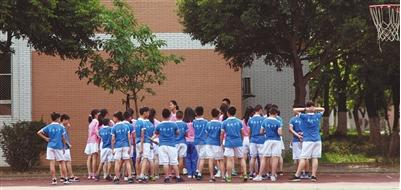 """6月8日,成都七中实验学校小学部,学生穿着印有""""成都七中""""的运动服在操场上上课。"""