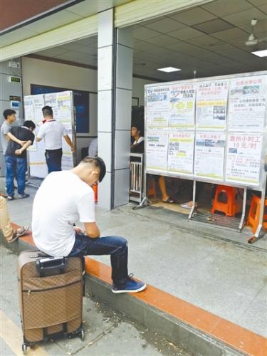 在三和市场找工作的年轻人,坐在行李箱上打起了盹儿