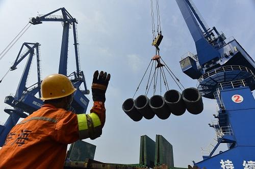 资料图片:在唐山港曹妃甸港区通用码头,工作人员在指挥大型起重机吊运钢材。