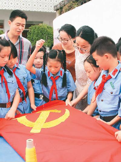 浙江省温岭市坞根红军小学师生在绣党旗。这面党旗是党的十九大收到的一件特别礼物。(新华社发)