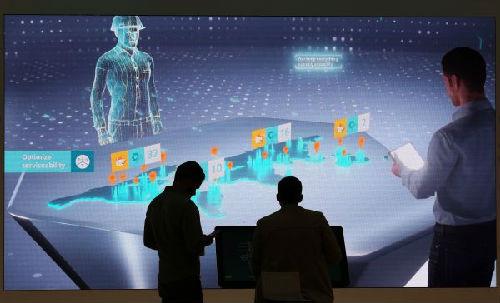 4月22日,在德国汉诺威工业博览会,两名男子在西门子展台检查互动屏幕。(新华/欧新)