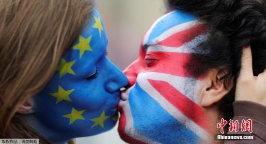 图为2016年6月23日,英国两个民众涂着欧盟旗帜和英国旗帜的脸谱深情一吻,满满的不舍。