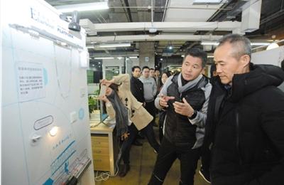 2017年,中国物联网产业技术创新战略联盟城市建设专业委员会主任蔡鸿岩(右二)与万科董事会名誉主席王石(右一)考察中国电科开放物联网智慧管理平台系统。 资料图片