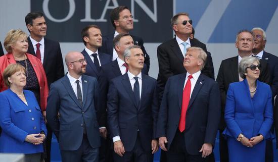 北约领导人们在峰会开幕前拍摄照片,大部分领导人似乎都在关注位于他们左侧的事物,但只有特朗普例外。