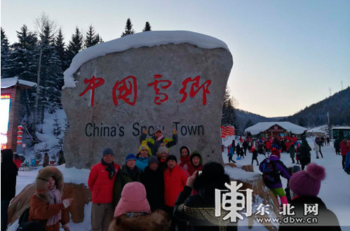 """抵达雪乡的游客在""""中国雪乡""""石碑前合影,见证到此一游。"""