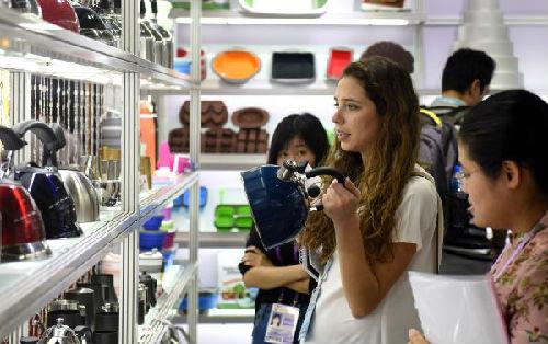 10月27日,在广州举行的第122届中国进出口商品交易会(简称广交会)上,外商在展馆里参观选购水壶。(新华社)