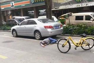 厦门:男子醉酒趴在车轮后 环卫大叔一旁守护他