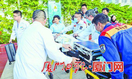 医疗团队将患儿送到急救车上。