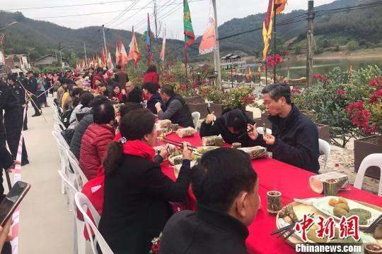 """200余名游客与畲族乡民们在长桌宴上同享""""山哈""""美食。 郑江洛 摄"""
