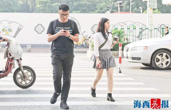 """昨日,天气炎热,市民夏装秋装各种""""乱穿衣""""出行。记者 陈理杰 摄"""