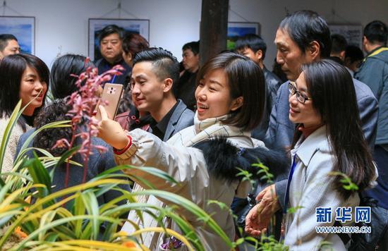 两名女士在花间拍照(3月8日摄)。新华网 肖和勇 摄