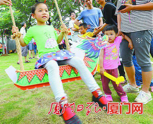 """在童趣龙舟乐园,孩子们坐在""""龙舟""""上荡秋千。"""