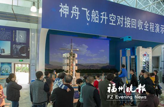 市民们观看神舟飞船升空对接回收全程演示系统。