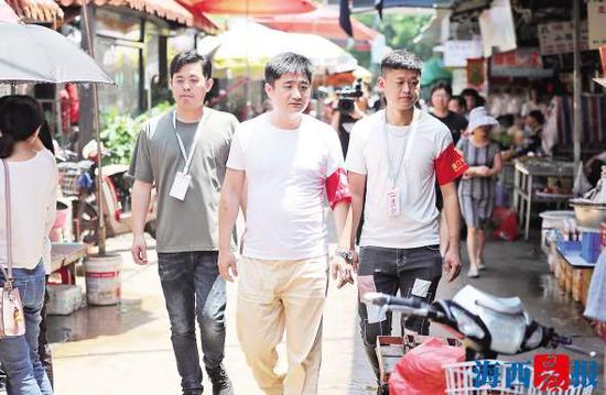 作为鹭江街道社区的平安志愿者,陈建阳(中)每天都会在市场周边巡逻。