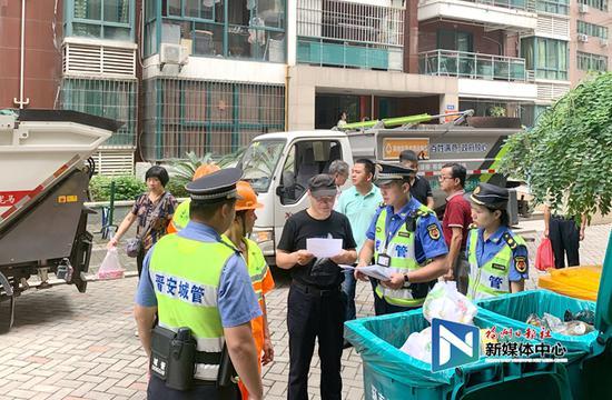 执法人员向物业下发责令限期整改通知书,向其宣传垃圾分类法律知识。
