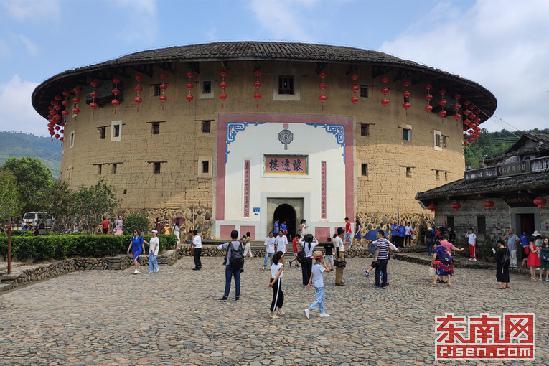 8月15日,游客在是建筑工艺最精美、保护最好的双环圆形土楼怀远楼前驻足、拍照。