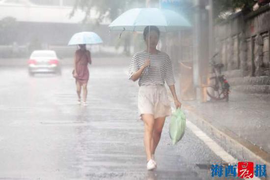 昨日下午,市民冒雨出行。记者 陈理杰 摄
