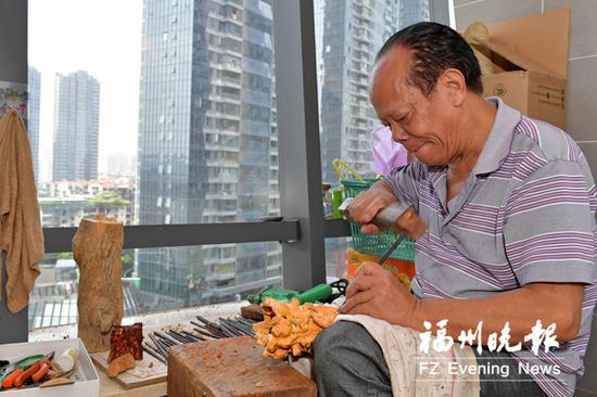 象园木雕老艺人叶祖应在做木雕。