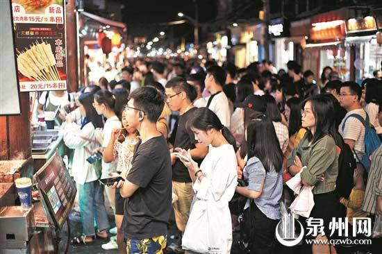 昨日晚上,西街一些小吃店前,游客排长队等待购买。(陈晓东 摄)