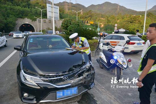 在贵新隧道口外,民警迅速处置追尾事故。