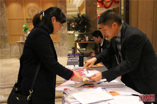 省政协委员王艳萍(左一)正在报到处报到。 东南网记者 林先昌 摄