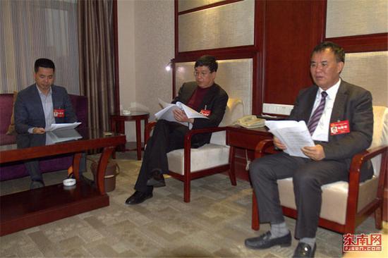 平潭代表团代表们报到后,交流《建议》。 东南网记者张立庆摄